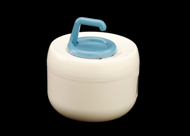 A blue adhesive plastic hook is affixed to the top of a cold cream jar. The hook allows Cindy to grasp and turn.