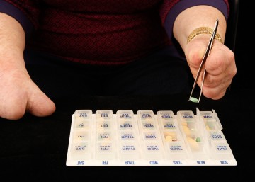 Cindy using a pair of all-silver tweezers to select pills from a clear plastic pillbox. The pillbox has days and times printed on small individual boxes, and a few of the boxes are open and showing pills of assorted sizes and colors (yellow, red, green). Cindy is using the tweezers with her left hand, and her torso is visible in the background. Her right hand is visible to the side.