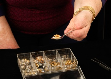 Cindy using a demitasse spoon to select gold earrings from a clear plastic earring storage box. The box has one cover and 12 slots, which contain silver and gold jeweled earrings. Cindy is using the demitasse spoon with her left hand, and it holds a couple of earrings in its bowl. Her torso is visible in the background. Her right arm is visible to the side.