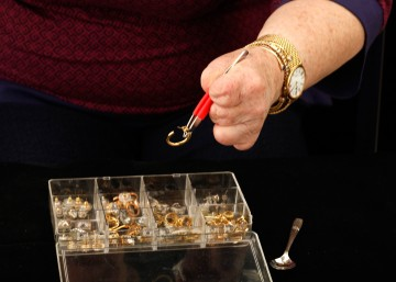 Cindy using the red-cushioned tweezers to select gold an earring from the clear plastic earring storage box. Cindy is using the tweezers with her left hand, and it holds one gold hoop earring. Her torso is visible in the background, and the demitasse spoon is on the side.