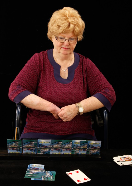Cindy sitting at a table with card holder in front of her, and cards played in front of her.