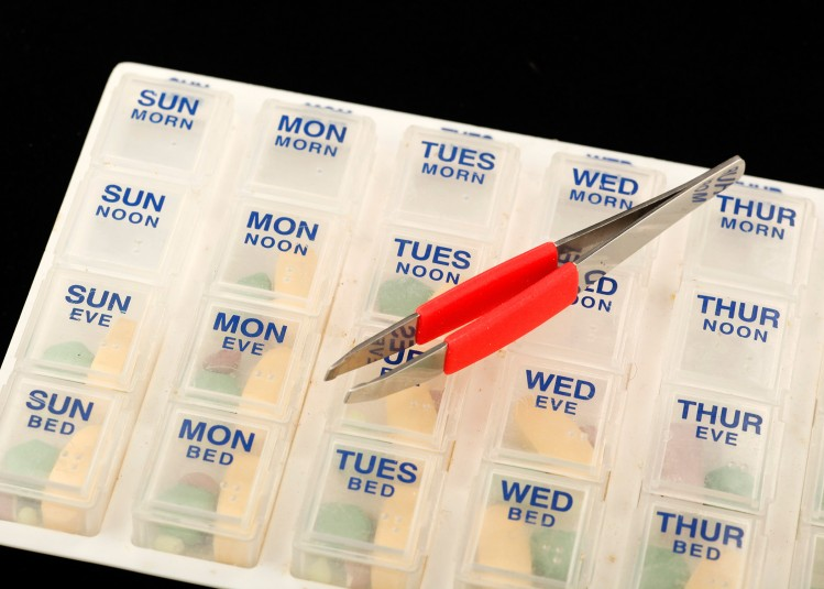 Close-up of the clear-plastic pillbox with a tweezers lying on top and all pillbox doors closed. The tweezers have a red soft grip.