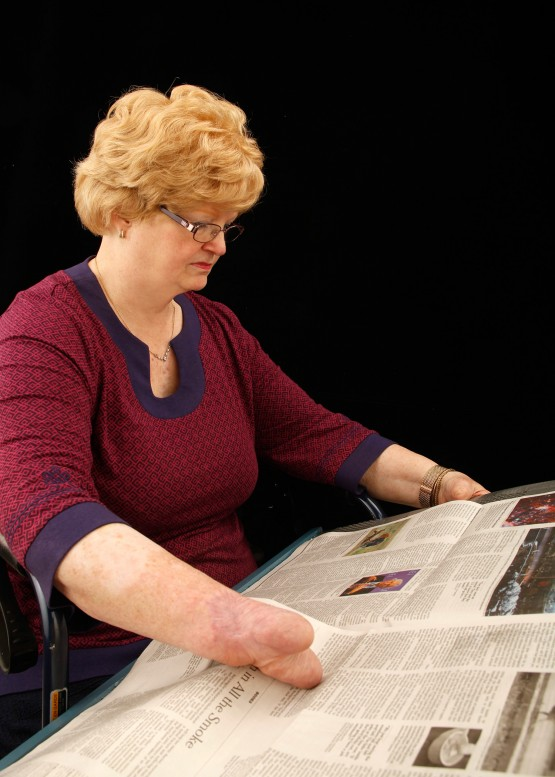 Cindy props the newspaper board on her lap. Its surfaces and structure allow her to view and page through a full size two page spread of a standard newspaper.