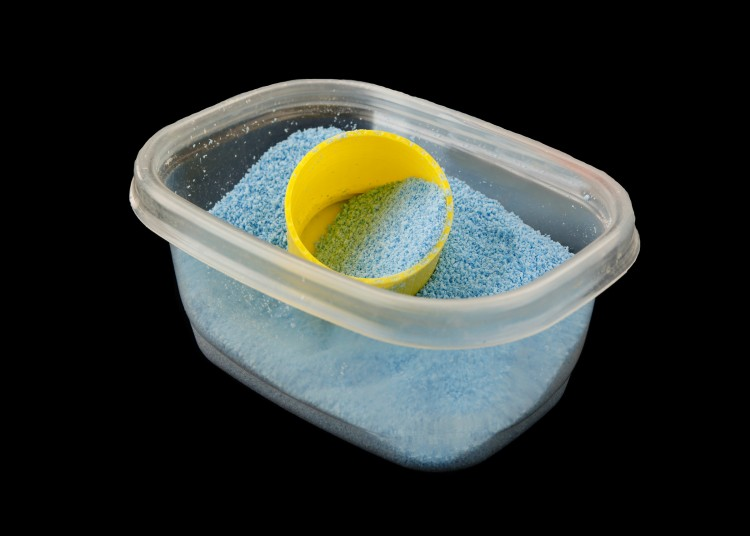 A studio shot of a rectangular plastic dish, normally used for food storage, containing 1-2 cups of powdered detergent. A small yellow measuring cup stands ready.