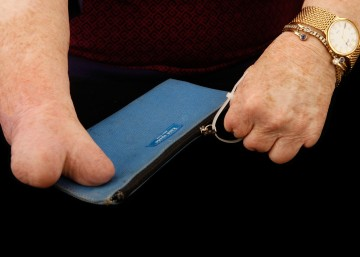 Cindy's right hand steadies a zippered purse, while her left hand grabs the cable tie and zips it shut.