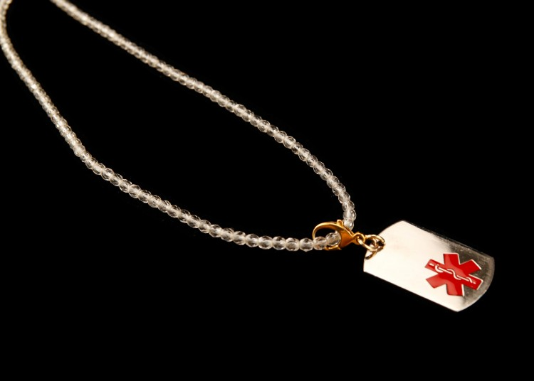 A necklace of clear plastic beads holds Cindy's medical ID tag.