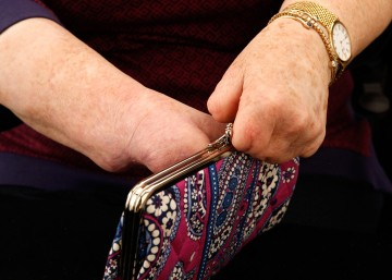 Another studio shot of Cindy's hands closing the purse.