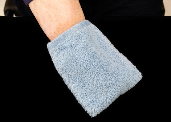 Cindy's hand covered by the blue washcloth. This is one of her key daily care devices.