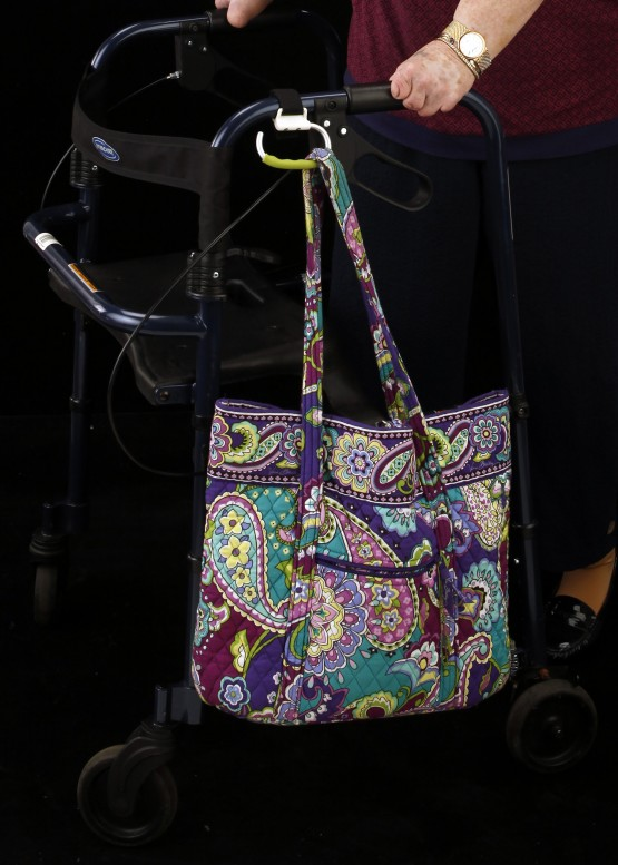 Studio close up of carabiner attached to the left handle of the walker, and angled down. It holds a paisley pastel-colored quilted cloth bag. Cindy'd hands are visible, holding the walker handles.