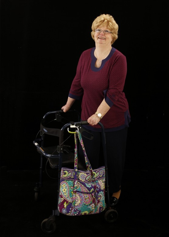 Studio shot of Cindy standing at her walker against a black background. Cindy is in a maroon shirt, is smiling at the camera, and has her two hands on the handles of the walker. The carabiner is attached to the left handle of the walker, and is angled down. It holds a paisley pastel-colored quilted cloth bag.