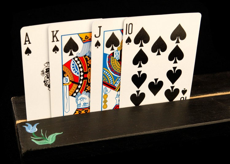 Close-up of the flower end of the card holder, with four cards visible (Ace, King, Jack, Ten).
