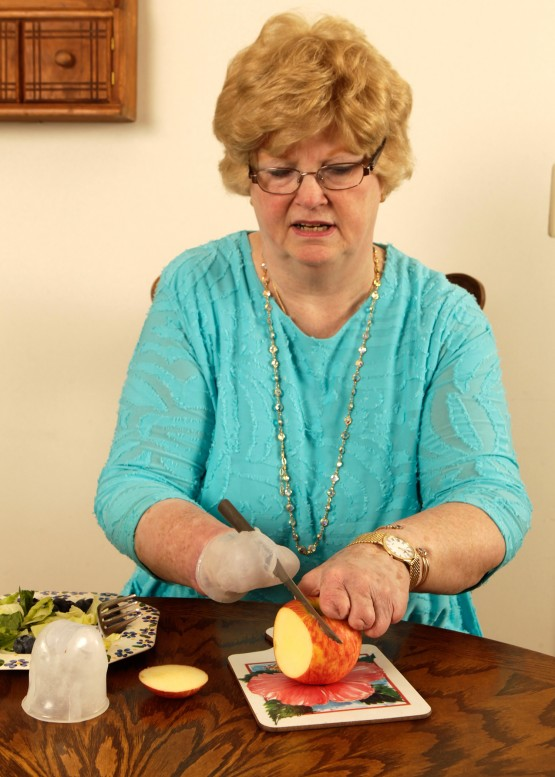 Shot from waist up of Cindy at a brown dining table, using the silicone knife unit to slice an apple. The knife is in her right hand and she uses her left hand to steady the apple as she cuts it with her right hand.  Nearby is the plate of food, the silicone fork unit, and a slice of apple that she already removed.