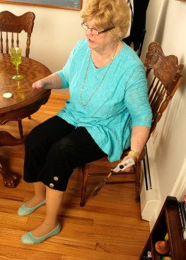 After donning both lower prosthetic legs, Cindy checks her attachments with a handheld