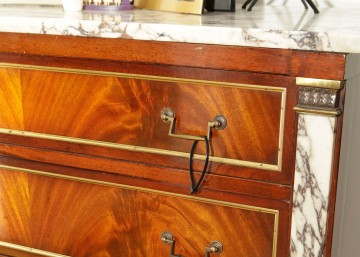 A shot of a wood and marble bureau with a cable tie hanging from the brass drawer pulls.