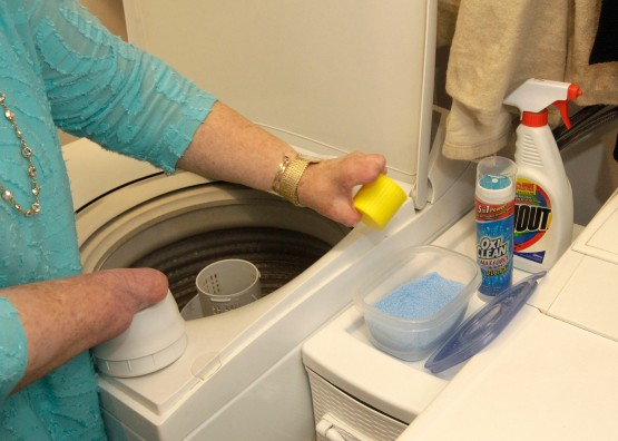 In Cindy's laundry room, Cindy stands with the yellow cup ready to dispense detergent in a way adapted to her body.