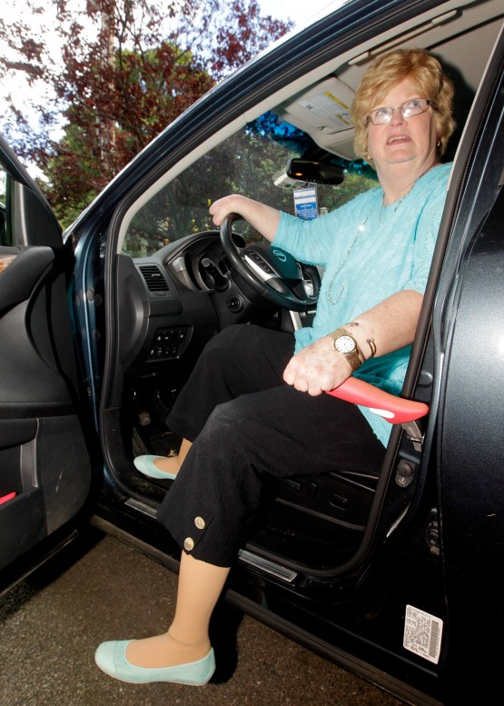 Cindy sitting in car with one leg in and one leg out, and one hand on the car assistance tool that is situated in the car's metal door-latch.