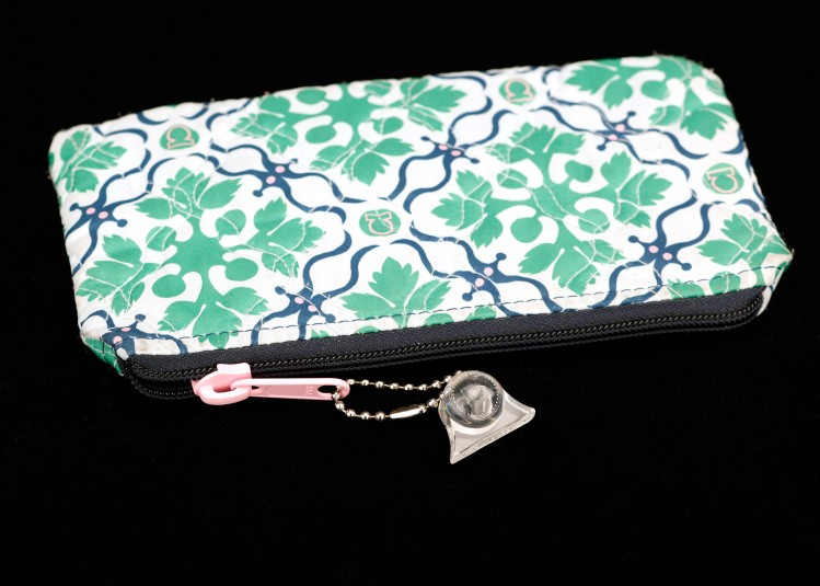 A flowered purse with a zipper opening. Cindy has attached a metal linked key chain with a clear plastic fob to the pink zipper pull.