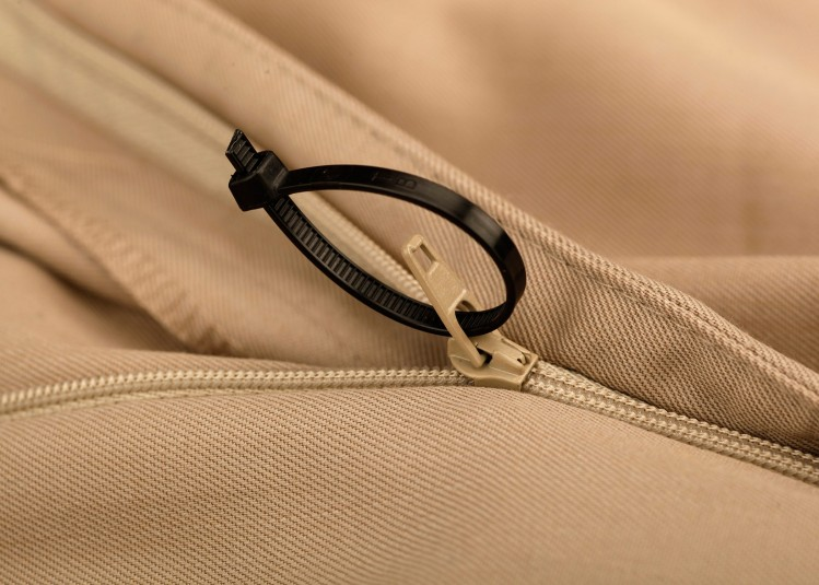 A small black plastic cable tie makes the zipper accessible on a pair of pants.