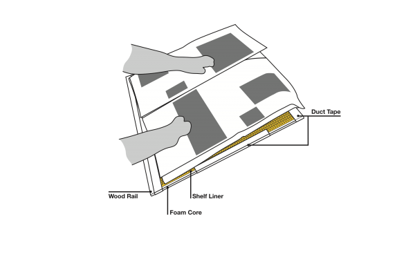 A technical drawing showing the layers and use of the newspaper board, with Cindy's hands able to manipulate the pages. Parts indicated are the wood rail at the bottom, the bottom layer of foam core, top layer of shelf liner, and duct taped sides and top edge.